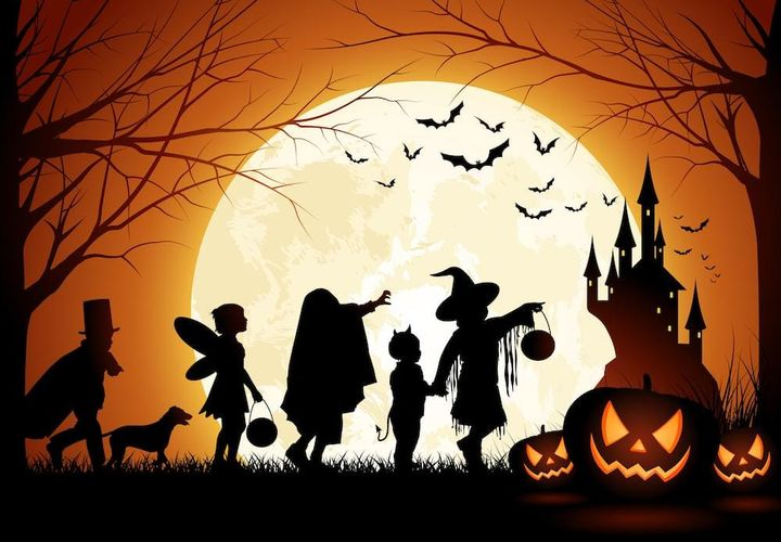 Halloween scene with carved candle-lit pumpkins and children in fancy dress pointing to turreted castle.