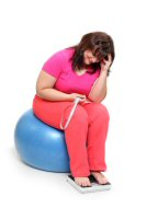 Woman sitting on exercise ball with tape measure